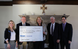 Members of Bangor Savings and SJC hold up the check for $5,000