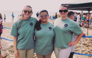 Olivia Marable '18 (center) with two other aquarium interns on the beach