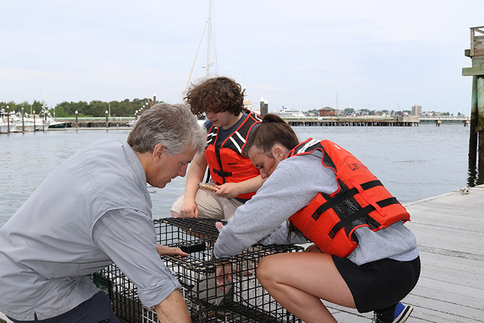 Professor Steve Jury, students Bailey Gryskwicz and David Glass work on a lobster trap for research
