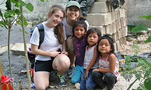 SJC students pose with Guatemalan children during a service trip to Guatemala.